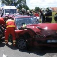 Autóbalesethez kiérkezett mentők mentenek az anyósülés felől.