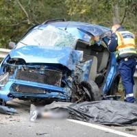 Felismerhetetlenségig összetört autó utasterét helyszíneli a kiérkező rendőr.