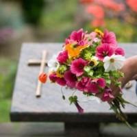 Egy csokor virág háttérben egy sírkővel.