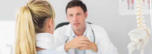 Egy orvos konzultál egy betegével a rendelőben, akinek a nyakán nyakmerevítő található. Feltételezhető, hogy gerincsérülés érte az áldozatot.