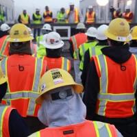 Üzemben dolgozók védőfelszerelésben állnak, feltételezhetően egy baleset körül.