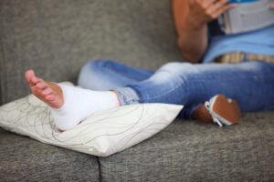 Eltört bokájú nő felpolcolta a lábát egy párnára.